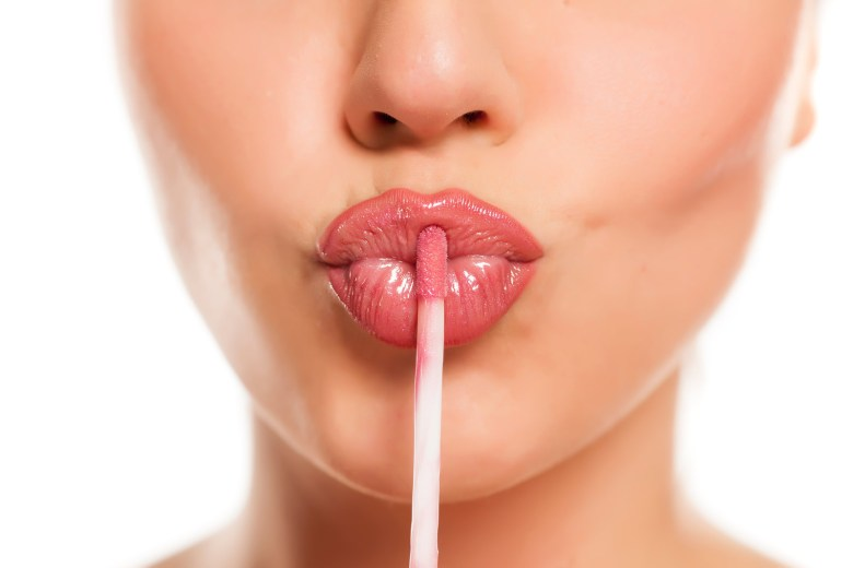 A woman applying lip gloss