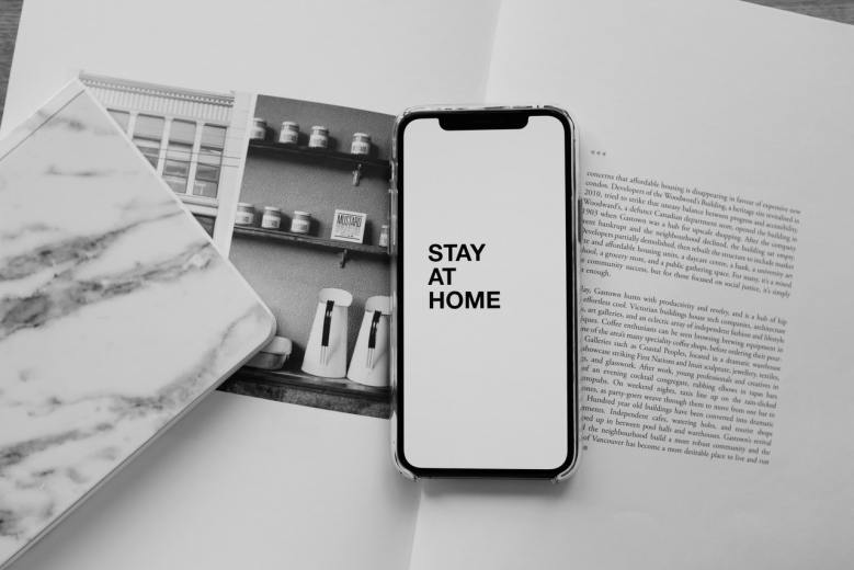"""A phone on top of an open book with the words """"Stay at Home"""" displayed on its screen"""