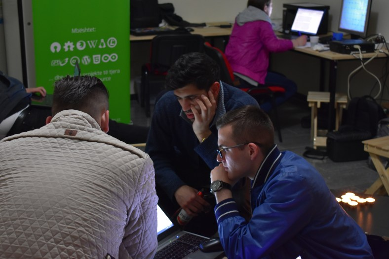Anxhelo Lushka helps two participants after midnight to help work through some problems in their project