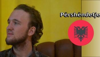 Përshëndetje nga Tiranë. Justin is pictured to the left of a rounded (circular) version of the Albanian flag.