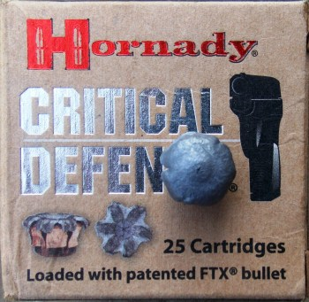 Box of Hornady Defense ammunition with an upset bullet on top