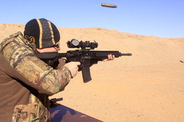 Dave Dolbee shooting an AR-15 rifle with a spent shell casing in the air