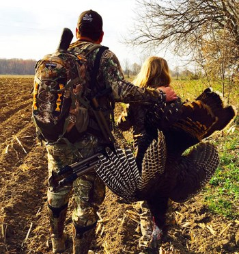 Father standing next to daughter who is holding a wild turkey slung over her back