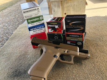 Glock 19X with several boxes of different brands of ammunition