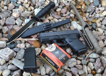 Glock 29 with a spare magazine, knives, and a box of federal Premium ammunition