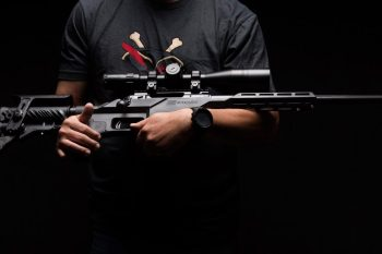 Man holding a Savage Model 10 BA Stealth rifle for Anti-Discrimination laws