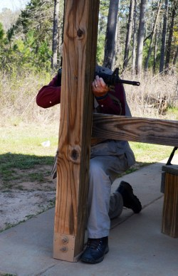 Bob Campbell shooting a rifle from behind a wood post for cover and concealment