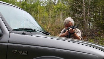 Bob Campbell shooting a rifle over the hood of a pickup truck