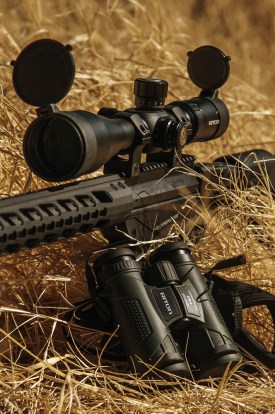 Riton optics AR-15 rifle topped with a rifle scope next to a binocular