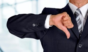 Man in business suit with a thumbs down gesture regarding Corporate America