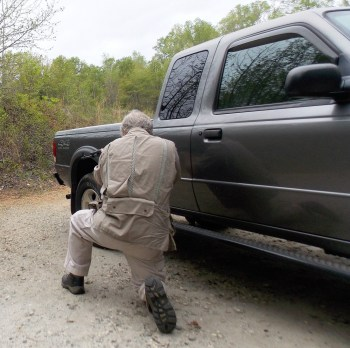 Firing an AR-15 from a kneeling position next to a truck
