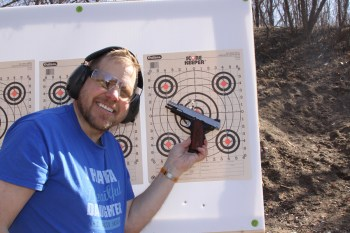 Dave Dolbee holding a Springfield EMP 4 pistol in front of a paper target