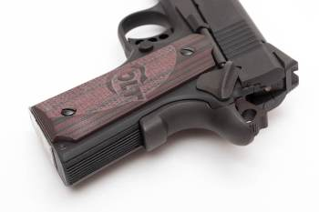 Grip serrations and beavertail safety of a Colt 1911 pistol.