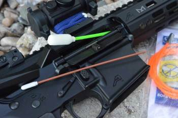 Swab-its bore cleaner being inserted into the bore of an AR-15 rifle
