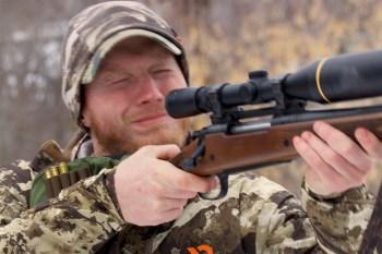 Man flinching while shooting a rifle