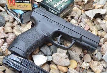 Walther Creed 9mm pistol right with a spare magazine and boxes of ammunition