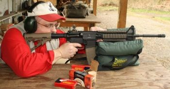 Dave Workman shooting an AR-15 from a benchrest at a talk about Universal Background Checks
