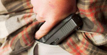 Concealed handgun being drawn from waistband
