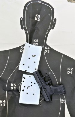 pistol atop a silhouette target with bullet holes