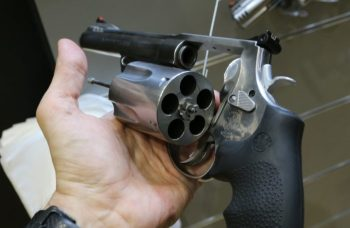 Hand holding a revolver with the cylinder open