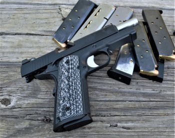 Guncrafter Commander 1911 pistil with slide locked back lying on several loaded magazines
