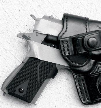 handgun with masking tape around it inserted into a black leather holster