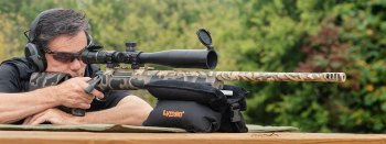 Man shooting a bolt action .30 caliber rifle from a shooting bench