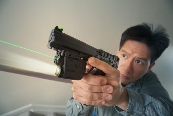 Asian man holding a pistol with a green laser beam