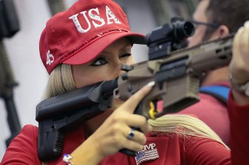 Woman holding an AR-15 wearing a ball cap with USA embroidered and a Trump 2020 logo on her shirt.