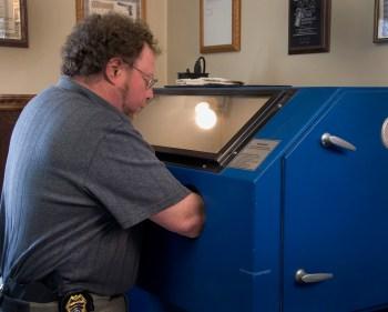 David Kenik working on a pistol in a sandblasting machine