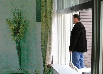view of a man standing at the front door of a house from a bedroom window