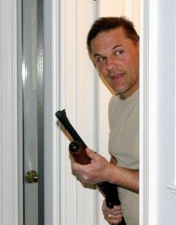 Man peeking through a doorway holding a shotgun