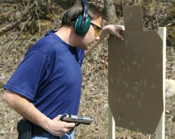 Man with one hand on a cardboard target and the other ready to fire his pistol from the retention position.