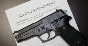 SIG Sauer pistol atop a copy of the Second Amendment