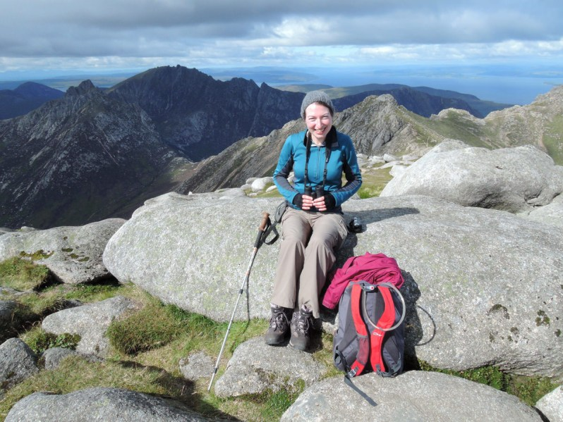A woman with binoculars, a rucksack and a walking pole sitting on a large boulder with the profile of jagged mountains beyond