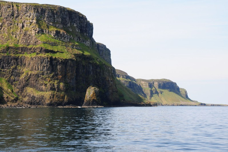 Impressive rocky sea cliffs with patches of grass on an island under a pale blue sky