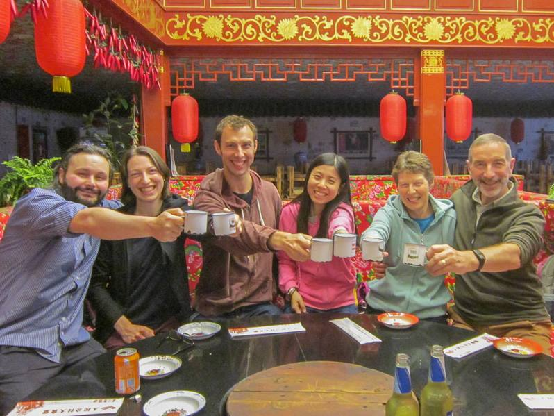 A family of six adults dressed casually sitting around a table in a Chinese restaurant holding cups with outstretched hands