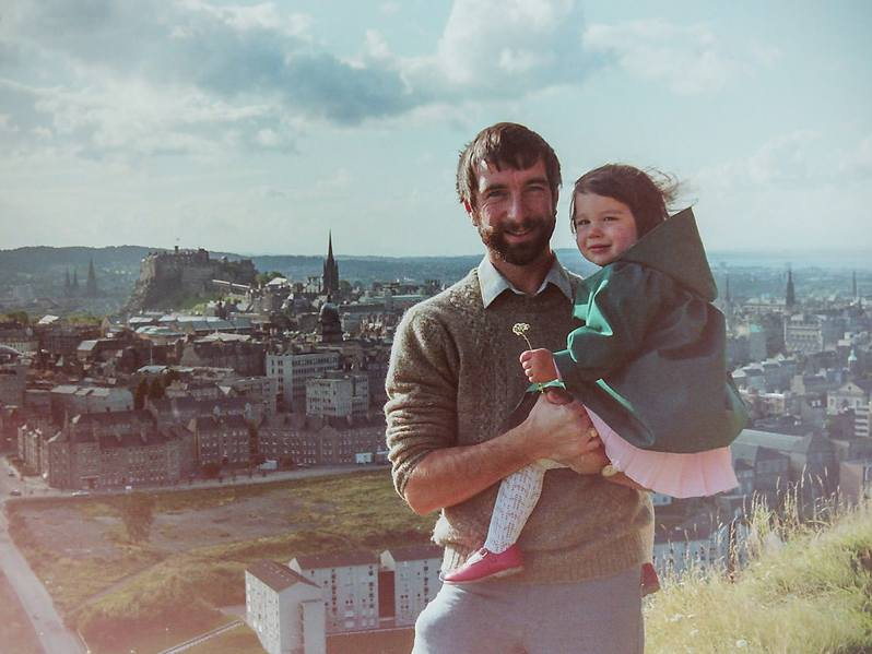 A young man with dark hair and a beard holding his toddler-age daughter with Edinburgh city skyline in the background