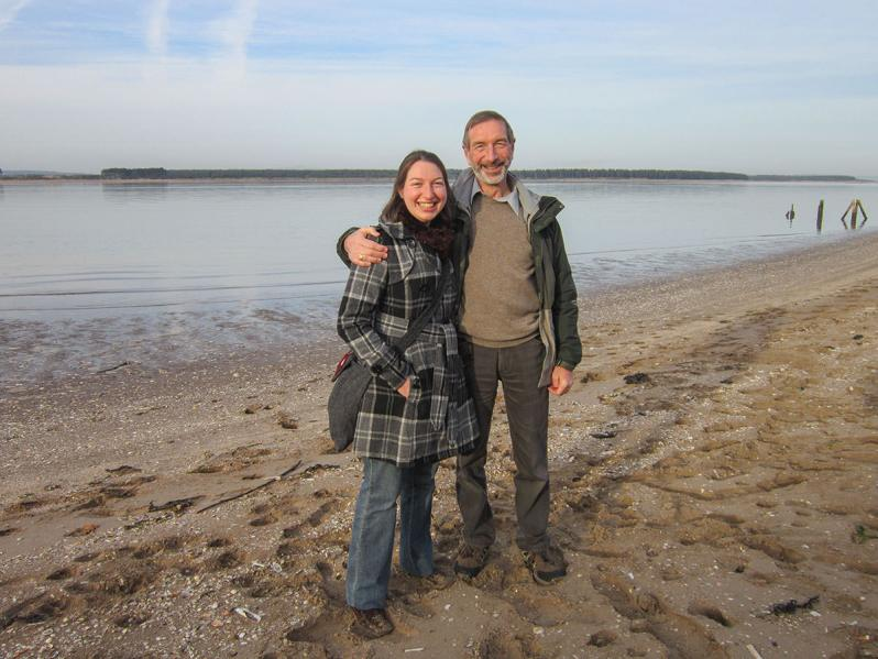 A father with his arm around his adult daughter, standing on a sandy beach with a bay and a line of trees in the background