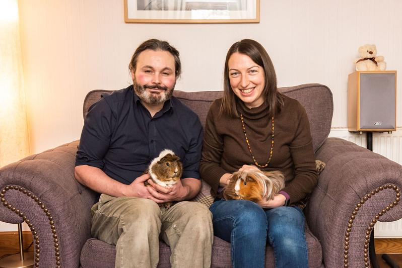 Family photo of blogger Karen Thorburn with her husband and two guinea pigs sitting on a lilac couch in pale pink lounge