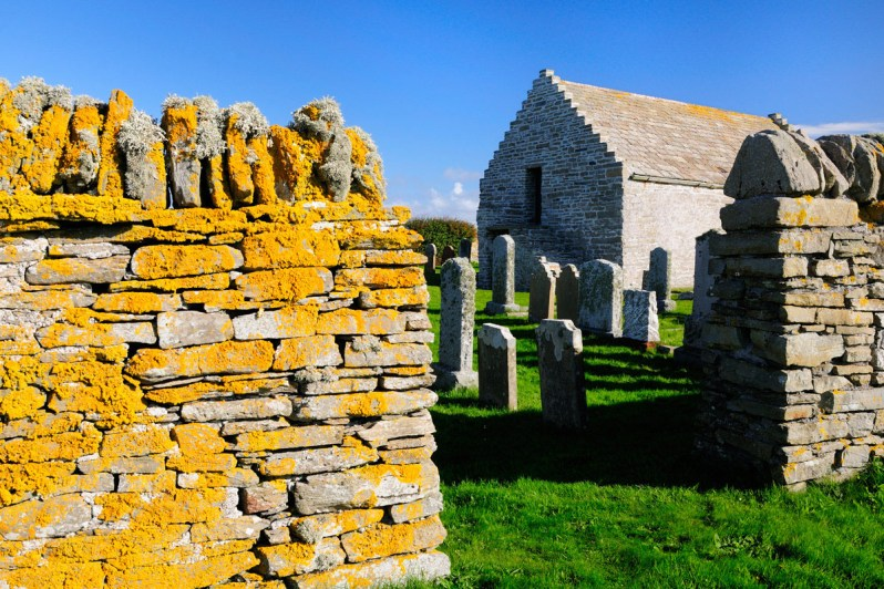 A dry stone wall covered in yellow lichen, with a grassy graveyard with headstones and a small stone church beyond