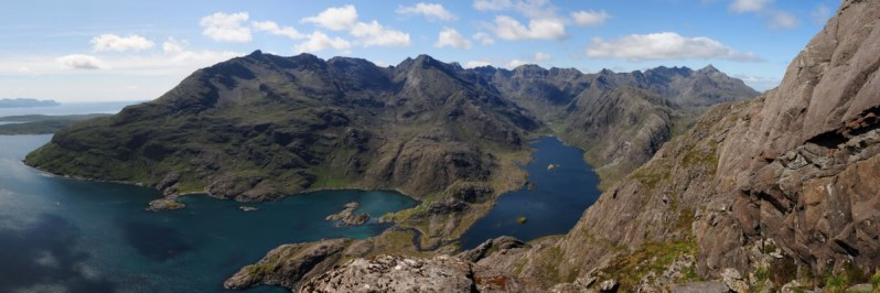 Panorama of a jagged mountain range, a sea loch and a freshwater loch, beneath a blue sky, with rocks in the foreground