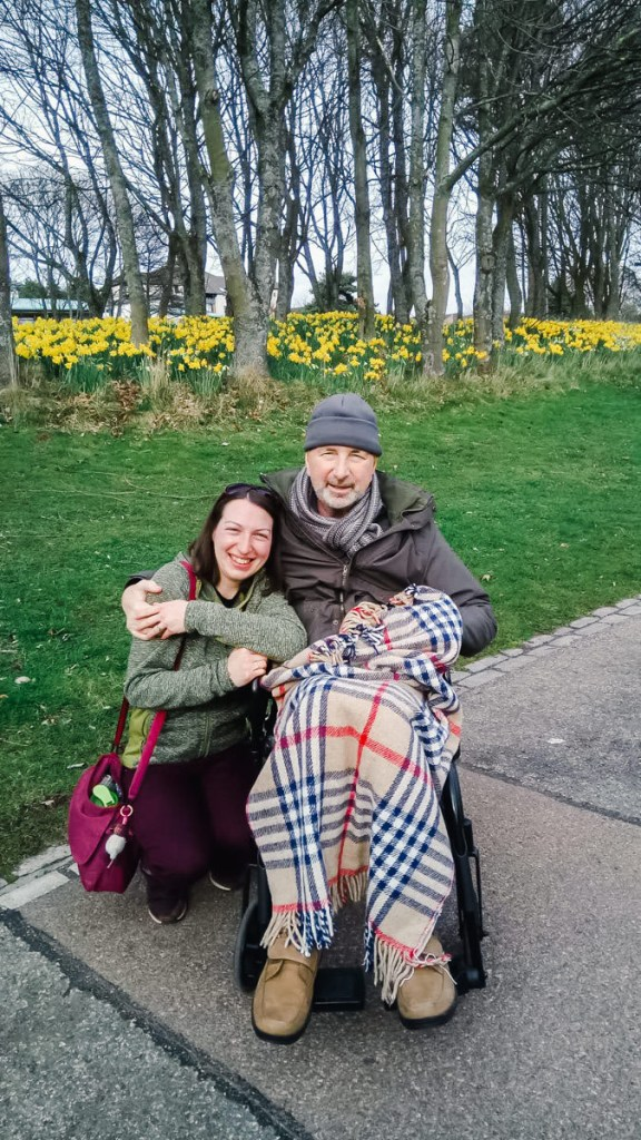 A young woman crouching next to a man in a wheelchair with a tartan blanket on a path in front of grass, trees and daffodils