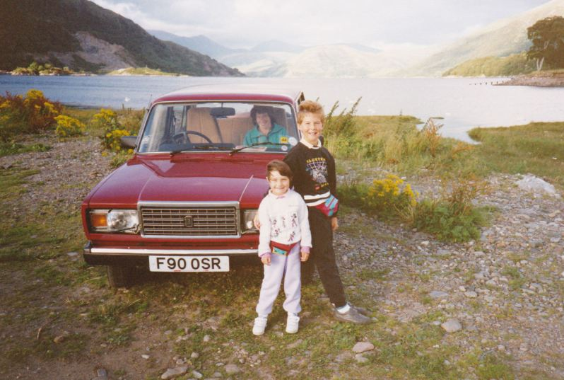 A young boy and girl standing in front of a red Lada Riva with a woman in the passenger seat, parked in front of a loch