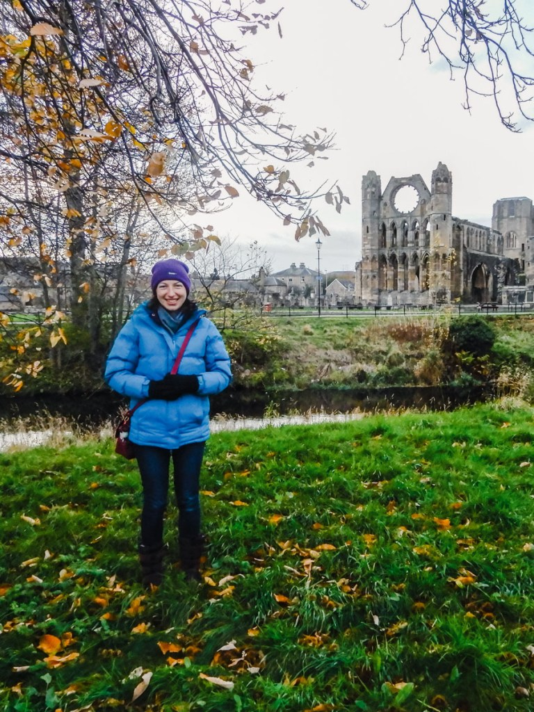A young woman dressed in winter clothes, standing on grass in front of a river with a ruined cathedral on the other side