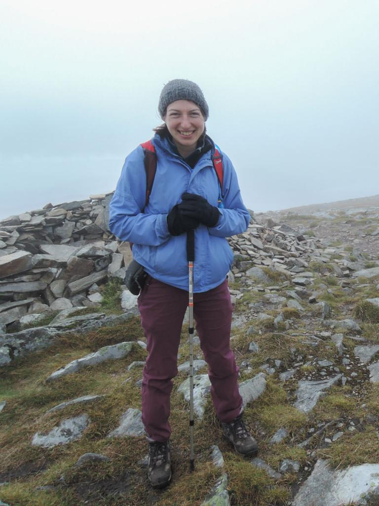 A young woman dressed in a blue cagoule and purple trousers, standing in front of a cairn on a mountain summit in the mist