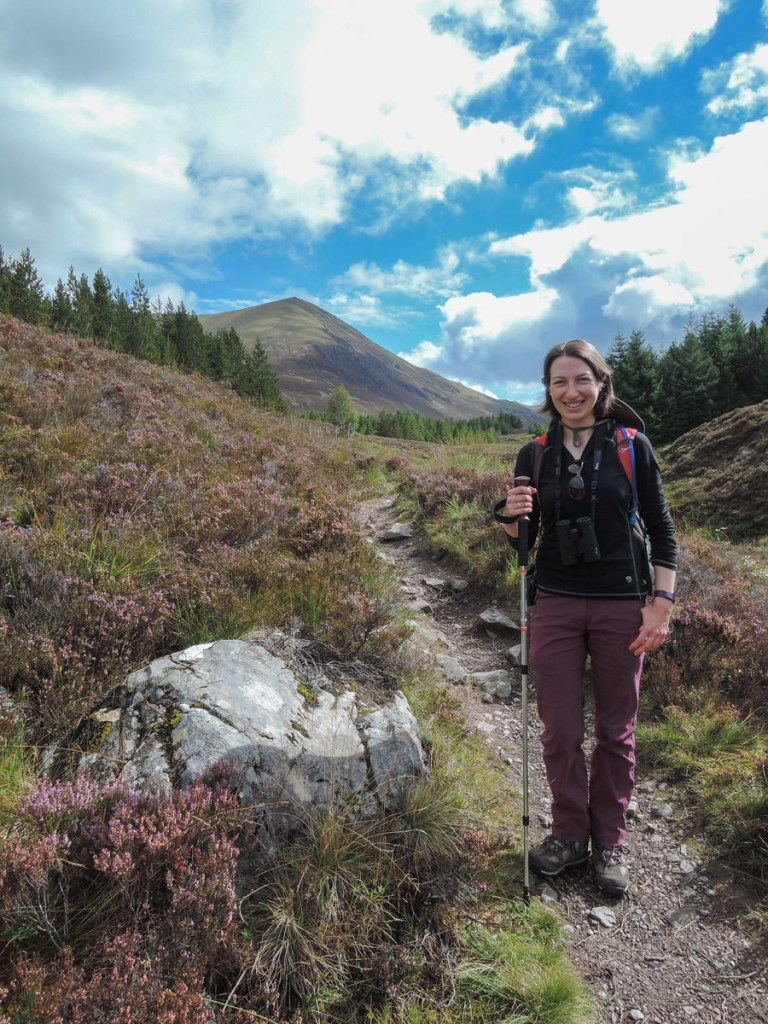 A young woman wearing outdoor clothing, standing on a rough path next to a boulder and heather, with a mountain beyond