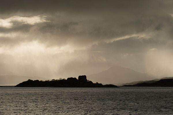 Small islands off the shore of the Isle of Lismore with rain clouds lit by the sun overhead