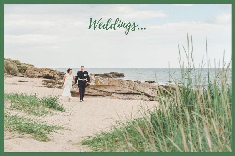 A bride and groom walking hand in hand on a beach in front of large rocks