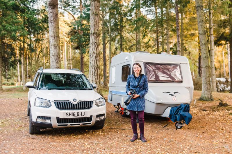 A woman smiling and holding a large camera, standing in front of a white car and small grey caravan in a woodland